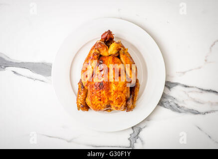 Rotisserie Chicken. Whole roast chicken on white plate seen from above on marble work surface - Stock Photo
