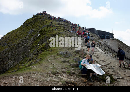 landscape image of female and male couple sitting down reading a map, Snowdon, North Wales,United Kingdom - Stock Photo