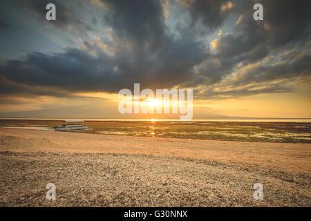Watching the sun set over Lombok on Gili Lampu Island - Stock Photo