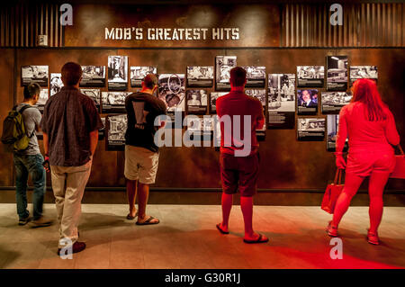 Visitors to the Las Vegas Mob Museum take in the Mob's Greatest Hits wall with horrific historic crime scene photos - Stock Photo