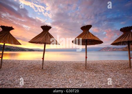 Straw umbrellas on the beach in Baska on island Krk - Stock Photo