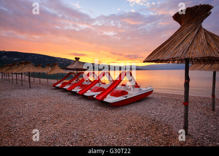Straw umbrellas and water pedal boats on the beach in Baska, island Krk - Stock Photo