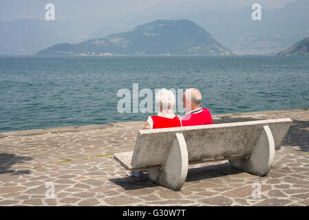 Elderly couple sitting  in the sun on park bench in Iseo on the shore of Lake Iseo, Lombardy, Italy - Stock Photo