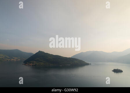 The islands of Monte Isola and Isola di Loreto at Lake Iseo with surrounding mountains and a glowing sky at sunset - Stock Photo