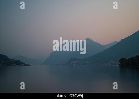 Tranquility over alpine mountains and villages and Lake Iseo at dawn in spring,Lombardy,Italy - Stock Photo