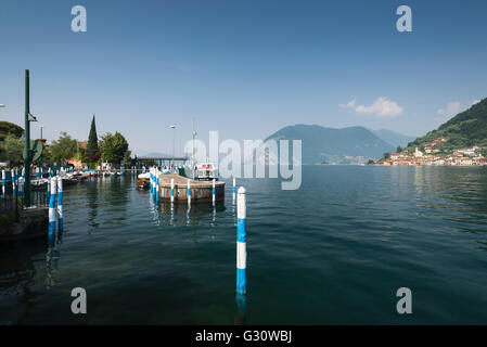 Colorful poles at the port of Sulzano on Lake Iseo with the panorama of Monte Isola and the rocky coast, Lombardy, - Stock Photo