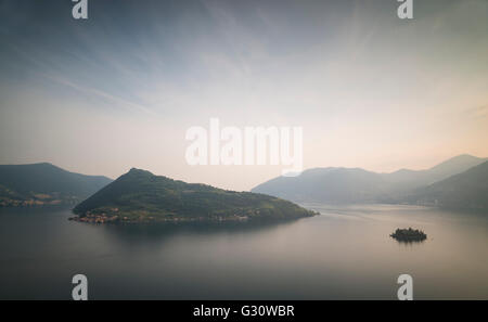 The islands of Monte Isola and Isola di Loreto at Lake Iseo with surrounding mountains and glowing sky at sunset,Lombardy,Italy - Stock Photo