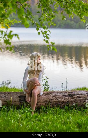 Handsome country-girl on lake river quiet riverside in beige dress mini short minidress curly curls blonde hair - Stock Photo