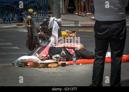 Homeless man sleeps on the ground just off Carmel Market (Shuk Ha'Carmel) area of Tel Aviv,Israel. - Stock Photo