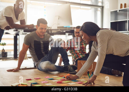 Group of four employees meeting around various colored sticky notes on hardwood floor in small office - Stock Photo