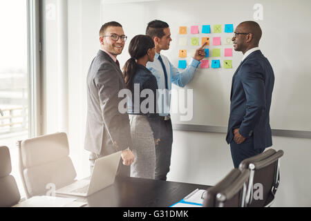 Cheerful group of diverse business people in conference meeting using colorful sticky notes to organize ideas on - Stock Photo