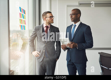 Two smart business managers or office co-workers in a discussion standing in front of a window with colorful memos - Stock Photo