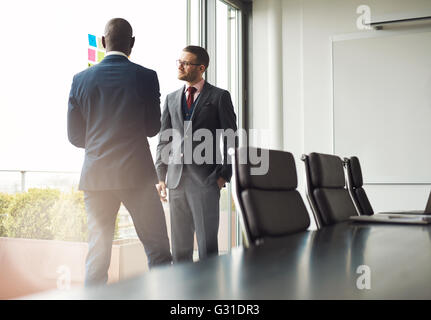 Two multiracial businessmen standing talking together in front of a window in a conference room, view over the table - Stock Photo