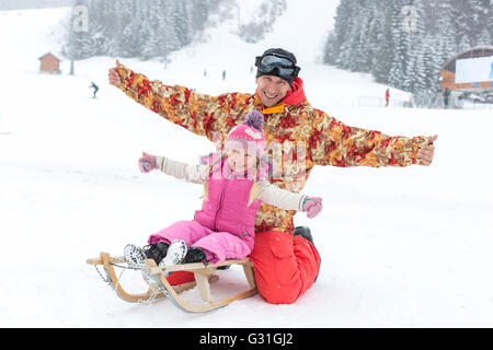 Dad and daughter posing sitting on a sled in the winter - Stock Photo