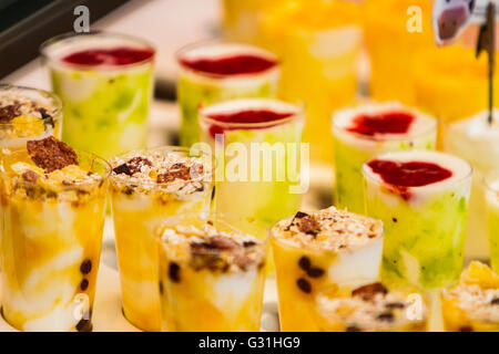 Frozen fruit smoothies with fresh blended different fruits served in tall glasses, summer sweet treat - Stock Photo