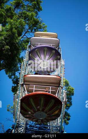 A colourful ferris wheel agains blue sky. A fair ride in amusement park carnival. - Stock Photo