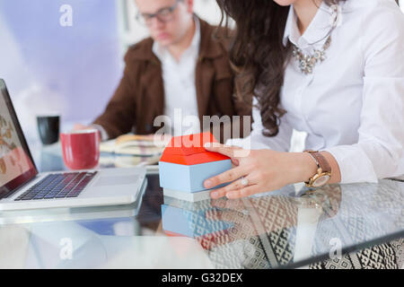 real-estate agent shows a build project on a digital tablet to a buyer - Stock Photo