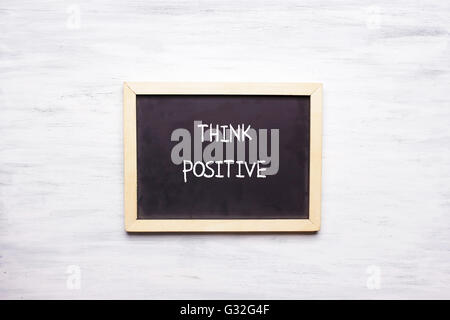 Top view of chalkboard with quote THINK POSITIVE written on it. Motivation and leadership concept. - Stock Photo
