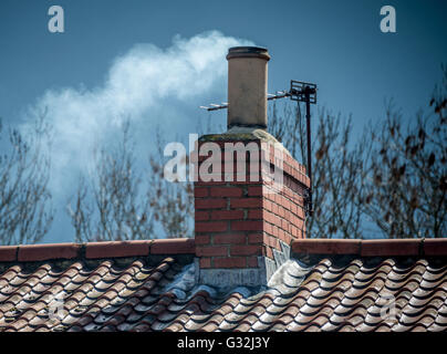 smoke billowing from a chimney pot on a roof top - Stock Photo