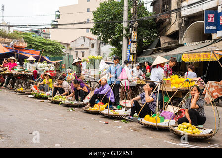 Fruit vendors in a street outside the famous Dong Xuan market in Hanoi Old Quarter. - Stock Photo