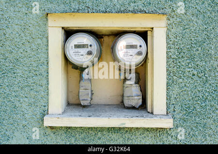Pair of digital electric meters on the exterior wall of a an old house - Stock Photo