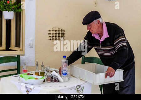 An Elderly Man Clearing Away Dishes At A Restaurant, Corfu Town, Corfu Island, Greece - Stock Photo