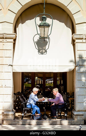 An Elderly Couple Drinking Coffee At A Cafe In The Fashionable Liston Area, Corfu Old Town, Corfu, Greece - Stock Photo