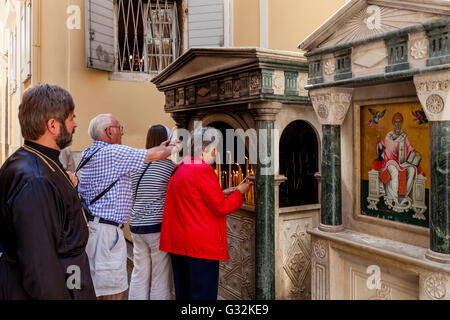Elderly People Light Candles Outside Saint Spyridon Church, Corfu Old Town, Corfu, Greece - Stock Photo