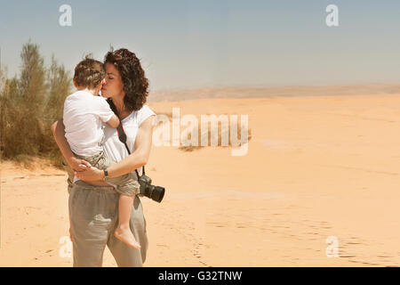 Mother standing in desert carrying her son, Jordan - Stock Photo