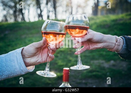 Two women making celebratory toast with glass of rose wine - Stock Photo