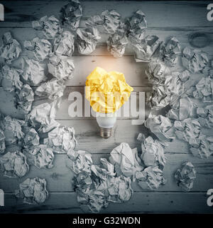 New idea concept with crumpled paper and light bulb - Stock Photo