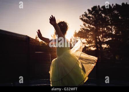 Girl spinning around in garden at sunset