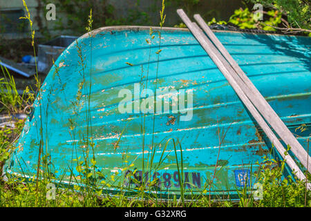 detail image of an old fiberglass boat laying in a overgrown yard - Stock Photo