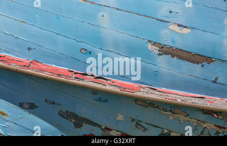 a detail image of an old wooden boat with peeling paint and signs of being exposed to the elements for years - Stock Photo