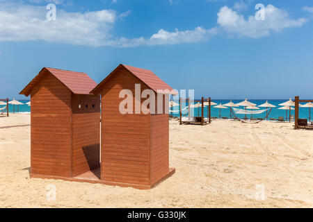 Two wooden beach huts with umbrellas on  sandy shore in Greece - Stock Photo