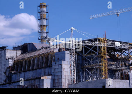 View of the concrete sarcophagus covering the damaged Reactor 4 of the former nuclear power plant located inside - Stock Photo