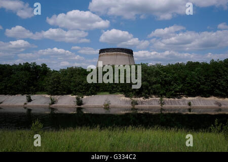 View of the cooling pond and the half built cooling tower of abandoned reactors 5 and 6 of the Chernobyl power plant - Stock Photo