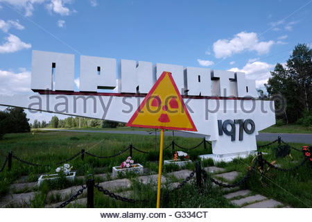 A sign warns of radiation at the city limit sign of the ghost town of Pripyat located near the border with Belarus - Stock Photo