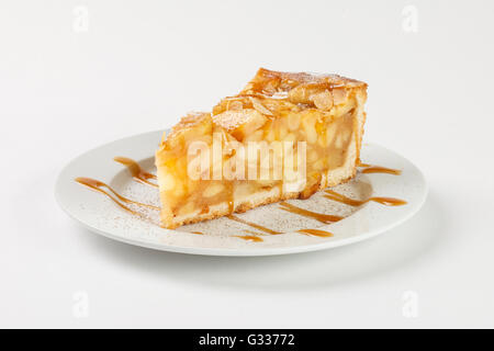 Delicious apple pie charlotte with caramel on the plate on white background. Close up side view.