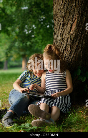 Brother and sister of 7-9 years sit under a tree and look in the tablet.Children with interest look at the screen - Stock Photo
