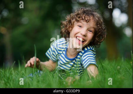 The boy of 8-9 years lies in a green grass and laughs. He has blond curly hair, a turned-up nose and blue eyes. - Stock Photo