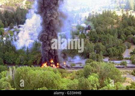 Black smoke pours from crumpled oil tankers after a fiery tanker train derailment June 3, 2016 in Mosier, Oregon. - Stock Photo