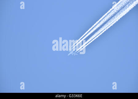White airliner transports passengers while it pulling white contrails in blue clear sky - Stock Photo