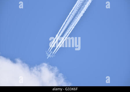 White airliner transports passengers while it is pulling white contrails in blue cloudy sky - Stock Photo