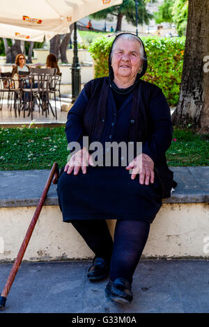 An Elderly Greek Woman Poses For A Photo, Corfu Old Town, Corfu, Greece - Stock Photo