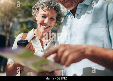 Middle aged couple looking at city map. Happy mature woman with her husband on a summer vacation. - Stock Photo