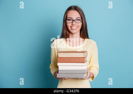Cute smiling girl holding many books isolated on the blue background - Stock Photo