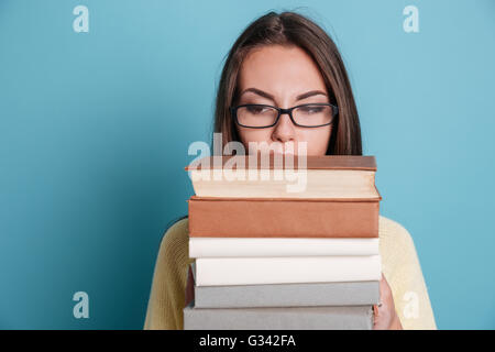 Close-up portrait of a girl in eyeglasses holding heavy books isolated on the blue background - Stock Photo