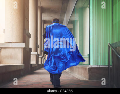 A business man is dressed as a super hero with a blue cape running in the city for a urgent job or leadership concept. - Stock Photo