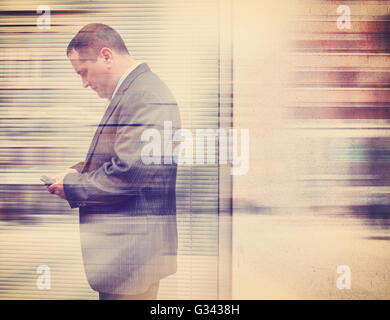 A business man in a suit is texting on his cell phone in the city outside with a wall for a communication or message - Stock Photo